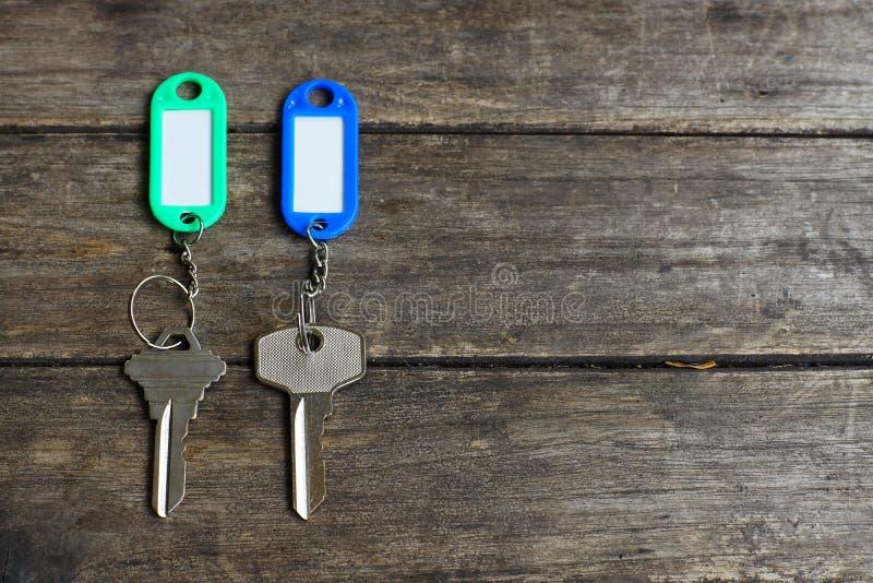 De huissleutels met kleur etiketteren sleutelring met groene tuinachtergrond, bezitsconcept, exemplaarruimte stock foto