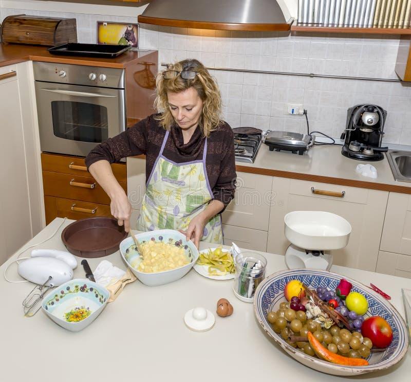 De huisvrouw bereidt een appeldessert in een slordige keuken voor royalty-vrije stock foto's