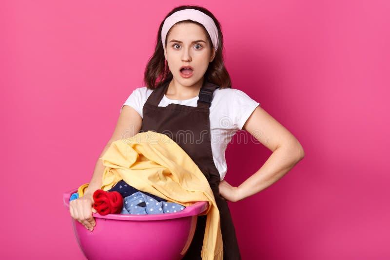 De huisvrouw houdt bassin vuile kleren, tribune met geopende mond, gelaatsuitdrukkingen geschokt, gekleed in bruin schort en haar stock afbeelding