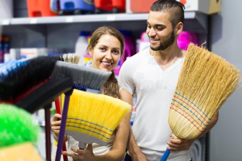 De huisvrouw kiest bezem voor het schoonmaken stock fotografie