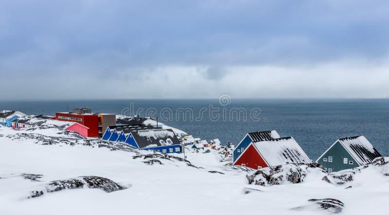 De huizen van het Inuitdorp die in sneeuw bij de fjord van Nuuk-stad, Groenland worden behandeld royalty-vrije stock afbeelding