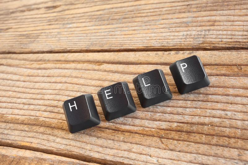 De HULP schreef met toetsenbordsleutels op houten achtergrond stock foto's