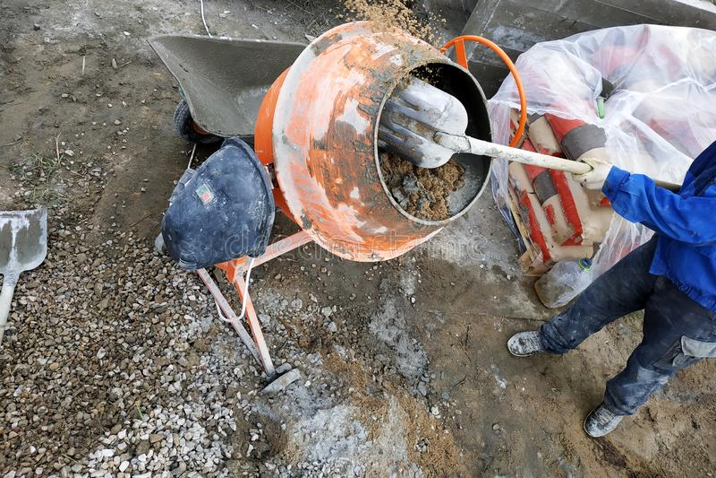 de hulparbeider gebruikt een schop om een cementmortier op een bouwwerf voor te bereiden royalty-vrije stock foto