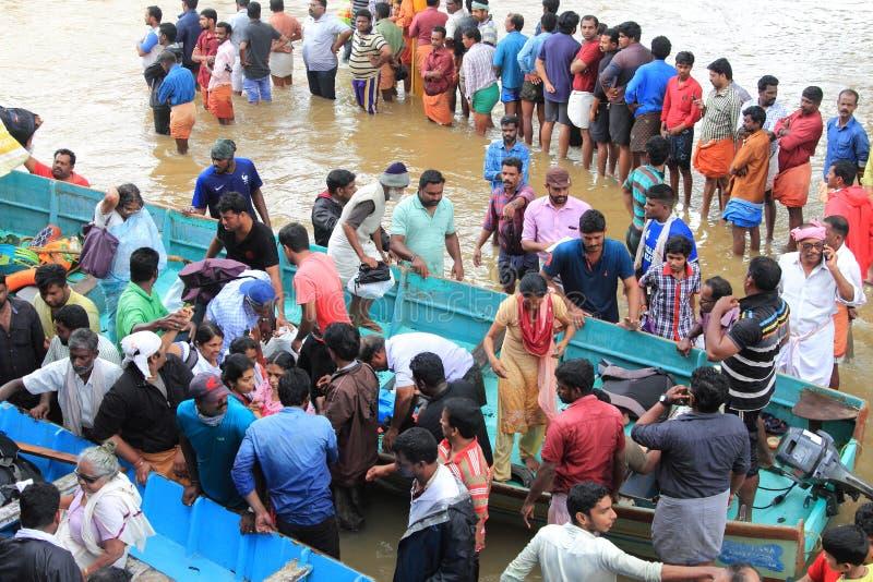 De hulpmensen van het reddingsteam aan vlucht van overstroomd gebied stock afbeeldingen