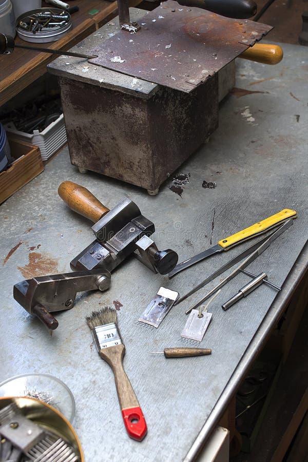 De hulpmiddelen, de componenten en de gebeëindigde vorm liggen op een bank in handcraft stock foto