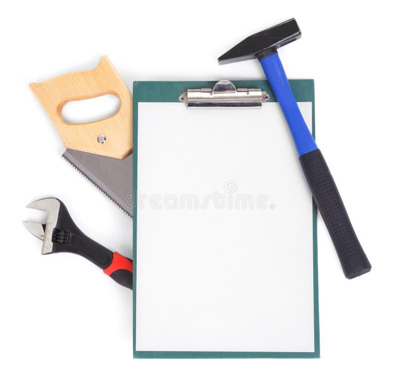 De hulpmiddelen en het klembord van het werk op wit royalty-vrije stock foto's
