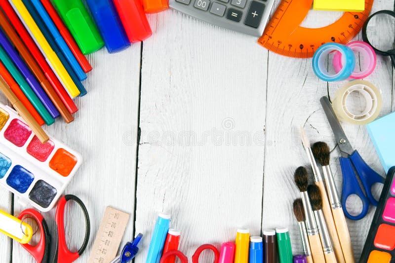 De hulpmiddelen van de school Op witte, houten achtergrond royalty-vrije stock afbeeldingen
