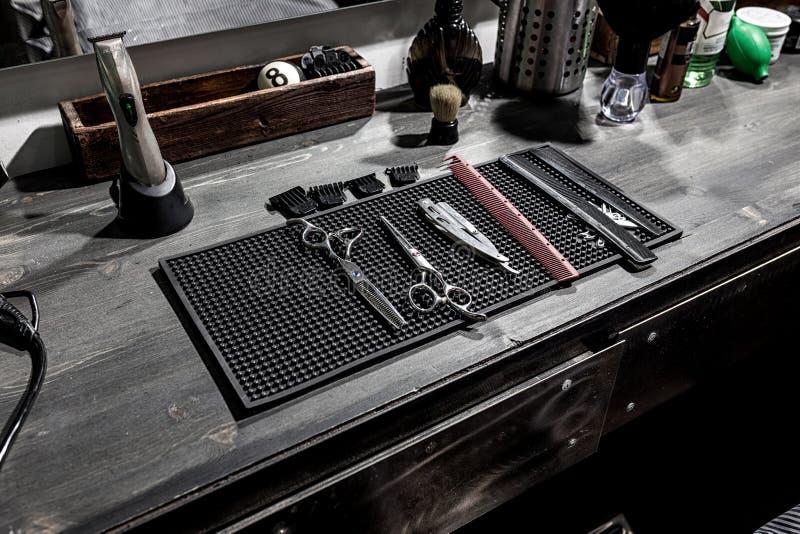 De hulpmiddelen van de kapper liggen op een zwarte mat op de Desktop royalty-vrije stock afbeelding