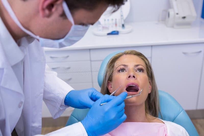 De hulpmiddelen van de tandartsholding terwijl het onderzoeken van vrouw bij medische kliniek stock fotografie