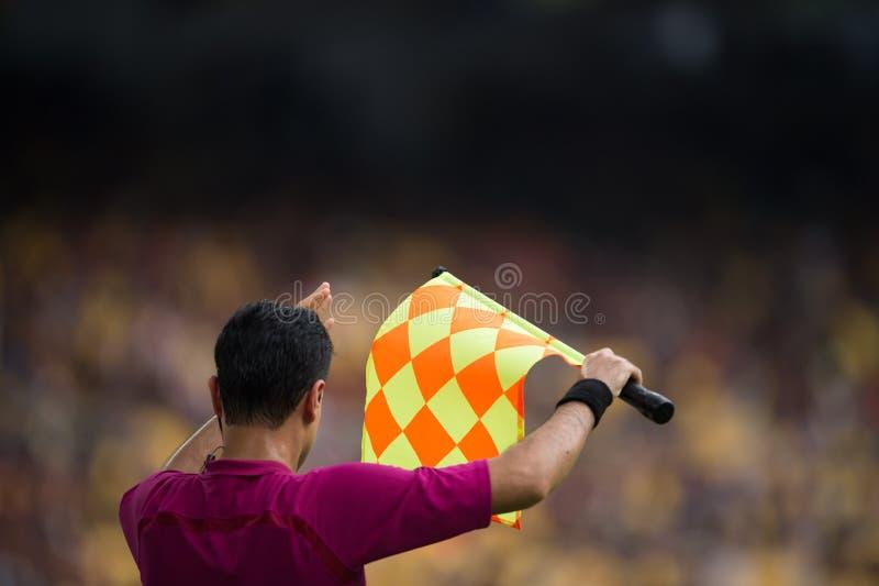 De hulpscheidsrechter houdt de vlag in stadion, voetbal royalty-vrije stock fotografie
