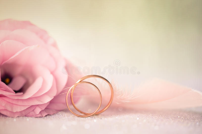 De huwelijksachtergrond met gouden Ringen en mooie Eustoma namen F toe stock afbeelding