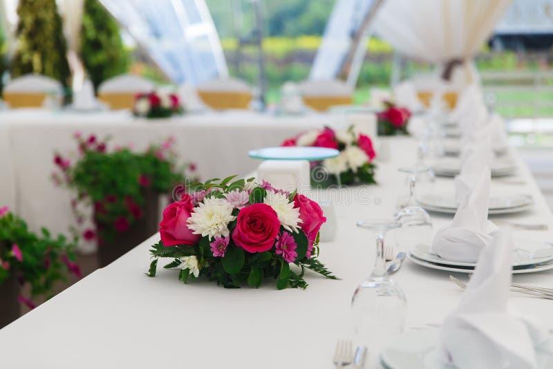 De huwelijksdecoratie, lijst die, op de lijst plaatsen is servetten en bloemen stock afbeelding