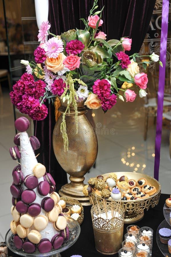 De huwelijksdecoratie met multicolored rozen in vaas, pastelkleur kleurde cupcakes, schuimgebakjes, muffins en macarons royalty-vrije stock foto