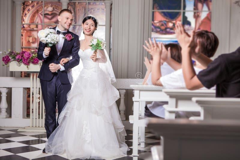 De huwelijksgasten die voor jonggehuwde toejuichen koppelen holdingsbloemen in kerk stock foto's