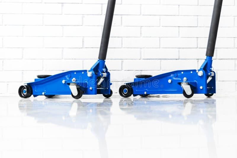 De hydraulische hefbomen van de autovloer Autolift Het blauwe Hydraulische de auto van Vloerjack for Herstellen Extra veiligheids royalty-vrije stock fotografie