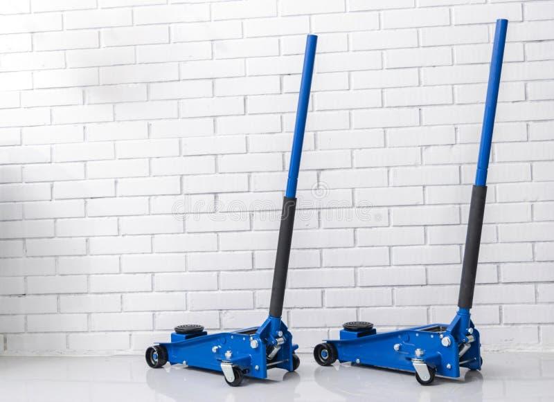 De hydraulische hefbomen van de autovloer Autolift Het blauwe Hydraulische de auto van Vloerjack for Herstellen Extra veiligheids stock fotografie