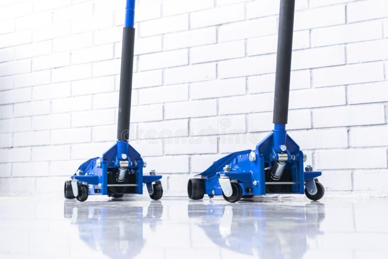 De hydraulische hefbomen van de autovloer Autolift Het blauwe Hydraulische de auto van Vloerjack for Herstellen Extra veiligheids stock foto's