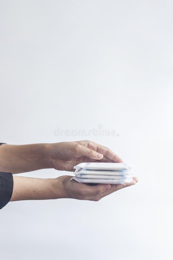 De hygiëneproducten van het wijfje De hand die van de vrouw een stapel maandverbanden houden tegen witte achtergrond Het concept  royalty-vrije stock fotografie