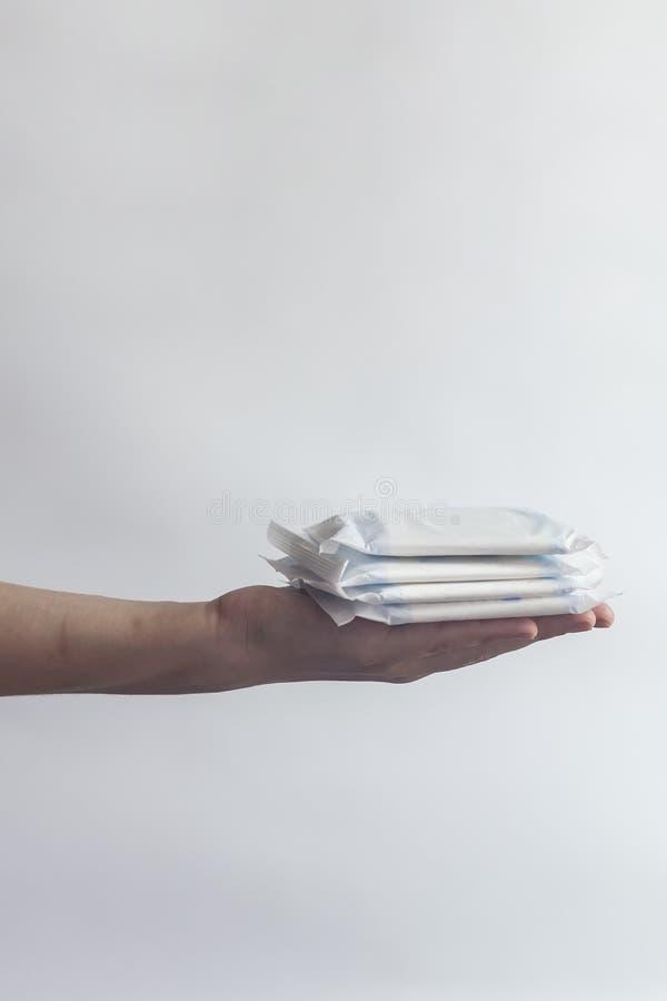 De hygi?neproducten van het wijfje De hand die van de vrouw een stapel maandverbanden houden tegen witte achtergrond Het concept  stock afbeeldingen