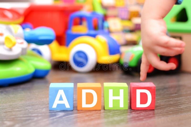 De Hyperactiviteitwanorde van het aandachtstekort of ADHD-concept met peuterhand wat betreft gekleurde kubussen tegen speelgoed royalty-vrije stock fotografie