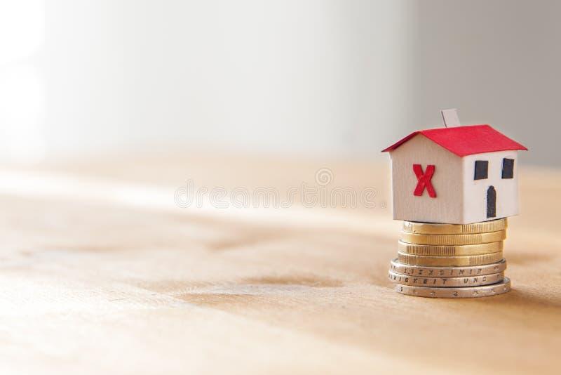 De hypotheek en de lening verwierpen concept: document huis op een muntstukstapel stock afbeelding