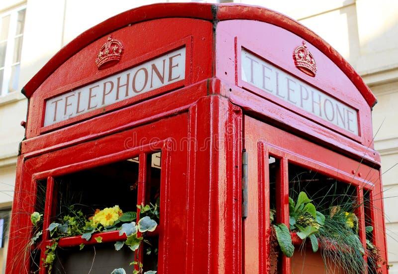 De iconische Britse rode telefooncel repurposed als bloemplanter stock foto