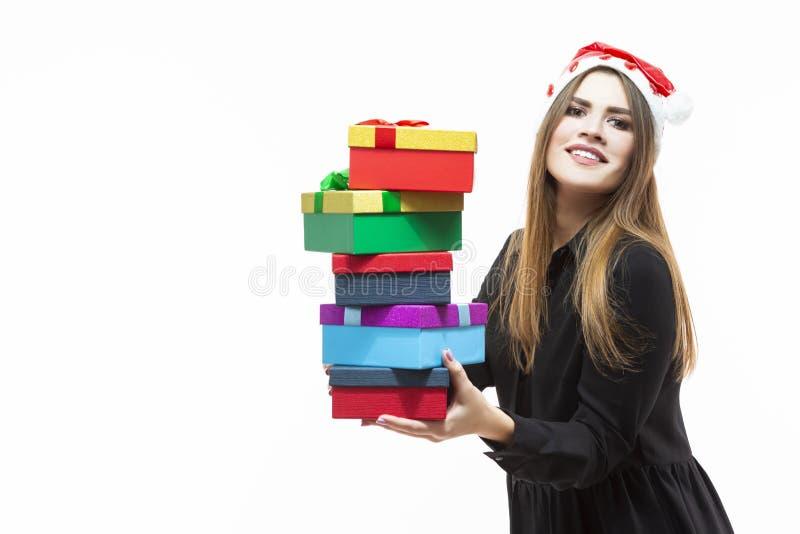 De Ideeën van de Kerstmistijd Portret van Gelukkige Kaukasische Donkerbruine Santa Girl Holding Heap van Kleurrijke die Giftdozen stock afbeeldingen