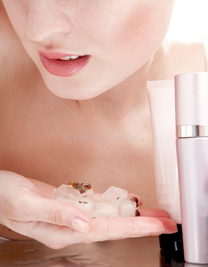 De ijsblokjes van de vrouwenholding dichtbij gezicht en schoonheidsmiddelen. stock foto