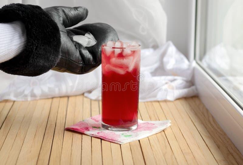 De ijsblokjes worden aan het glas met kersensap toegevoegd op het de wintervenster dat wordt gekoeld De handen van de kok zijn ge stock foto's