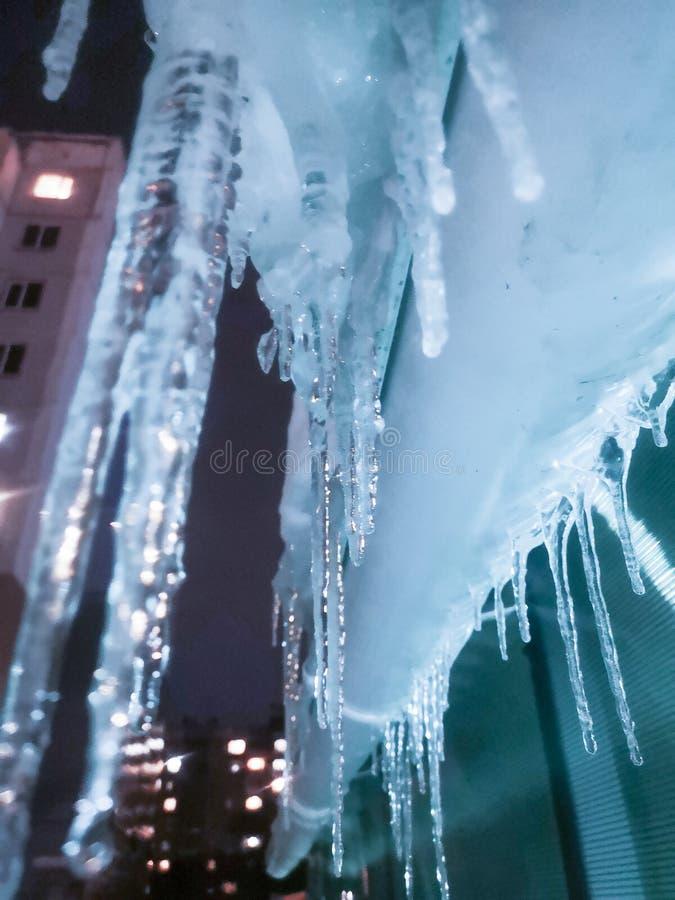 de ijskegels zijn de mooie lange winter hang van het dak van huizen foto stock foto