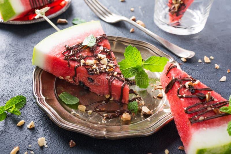 De ijslollys van de watermeloenplak met chocolade, noten en munt stock afbeelding