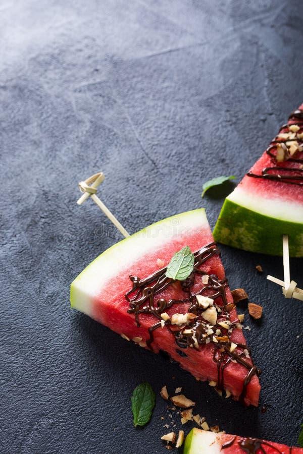 De ijslollys van de watermeloenplak met chocolade, noten en munt stock foto
