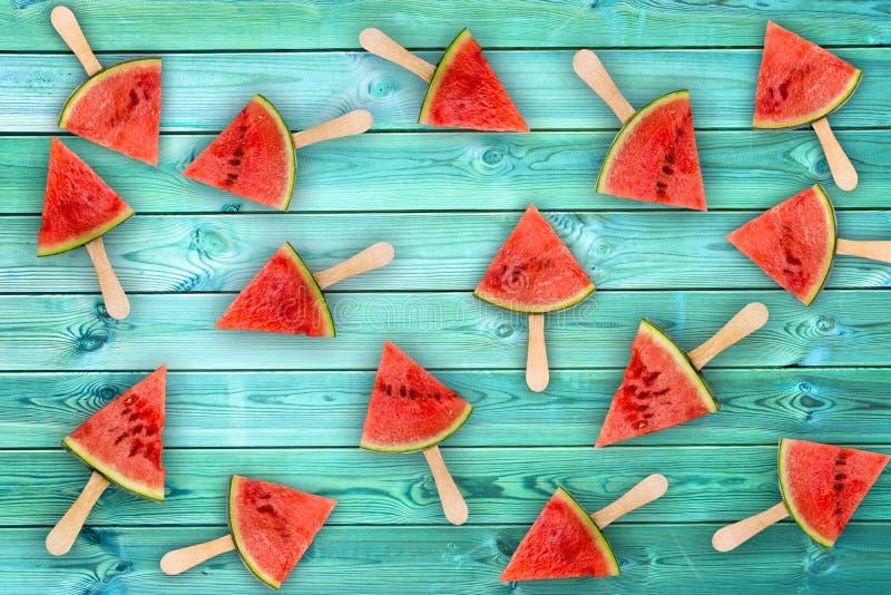 De ijslollys van de watermeloenplak op blauwe houten achtergrond, vers fruitconcept stock afbeelding