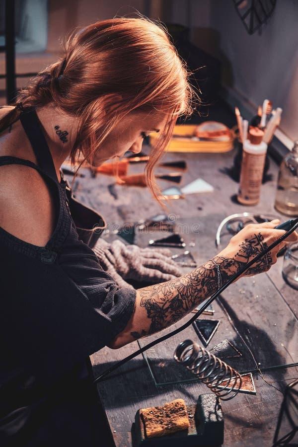 De ijverige vrouw werkt aan haar eigen project op glasworkshop royalty-vrije stock afbeelding