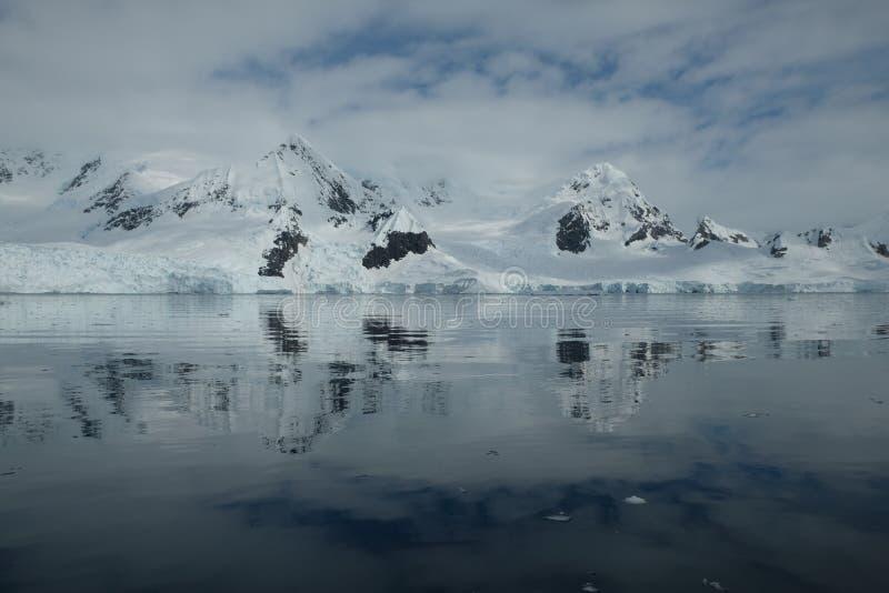 De ijzige bergen die van Antarctica in de spiegelbaai nadenken stock foto