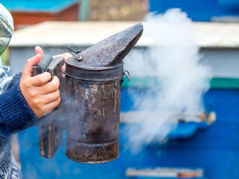 De imker houdt een schoorsteen in zijn hand voor beroking van bees_ royalty-vrije stock afbeelding