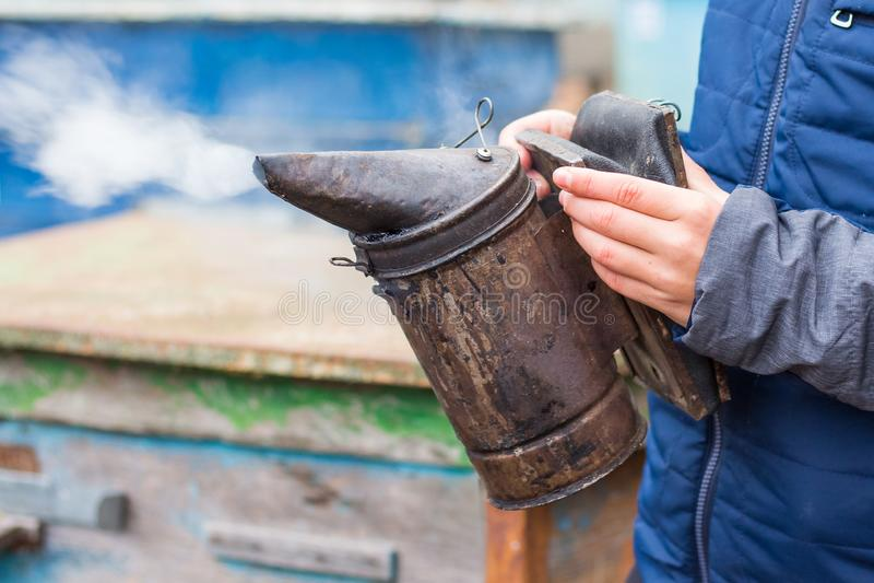 De imker houdt een schoorsteen in zijn hand voor beroking van bees_ royalty-vrije stock foto
