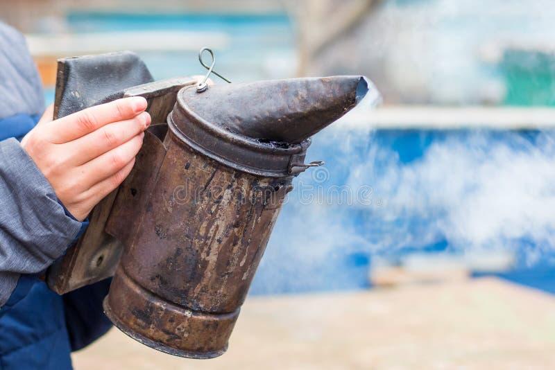 De imker houdt een schoorsteen in zijn hand voor beroking van bees_ stock afbeelding