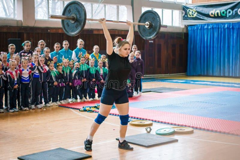 De indicatieve prestaties van weightlifters bij het kampioenschap in het cheerleading, jong meisje heffen een zware barbell op, b stock foto