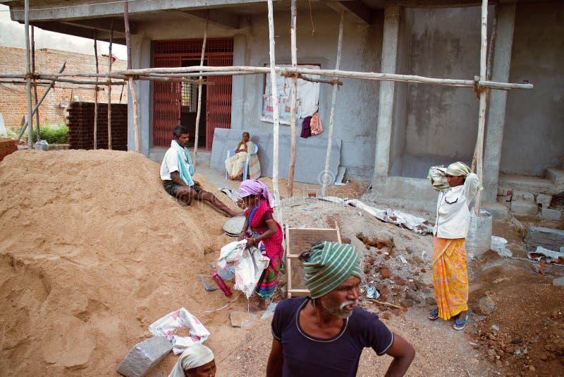 De Indische Arbeiders in bouw van concrete huizen dichtbij zand stapelen zich op royalty-vrije stock afbeeldingen