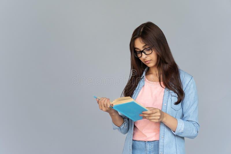 De Indische glazen die van de studentenslijtage die boek lezen op grijze studioachtergrond wordt geïsoleerd royalty-vrije stock afbeeldingen