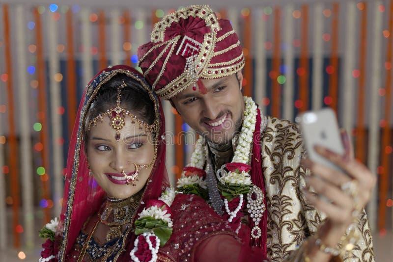 De Indische Hindoese Bruid & verzorgt het gelukkige het glimlachen paar schieten zelf met mobiel. stock foto's