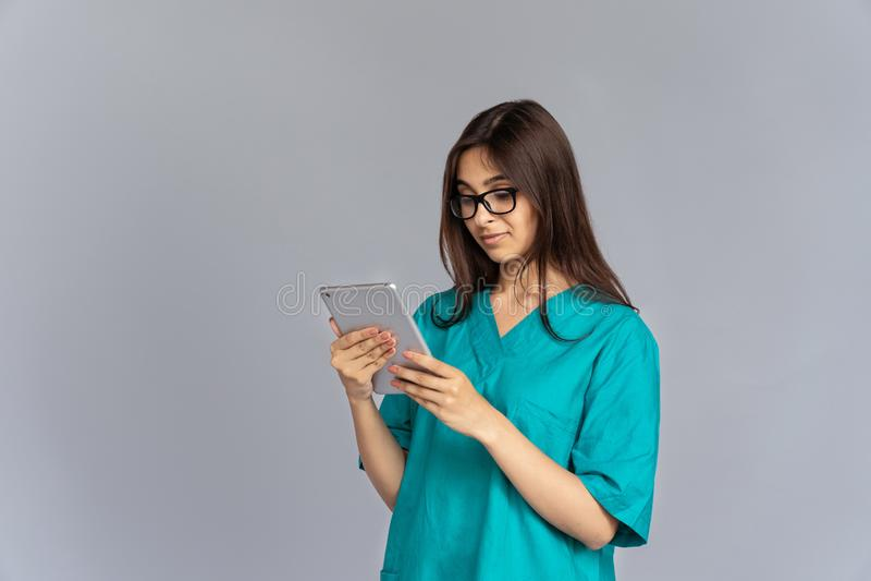 De Indische holding die van de vrouwenverpleegster digitale die tablet gebruiken op studioachtergrond wordt geïsoleerd royalty-vrije stock afbeeldingen