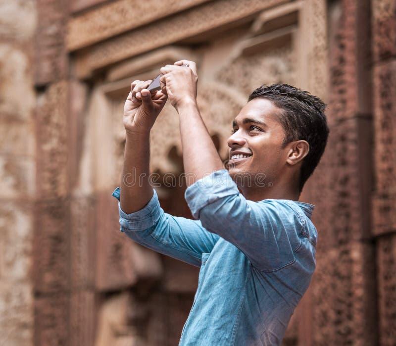 De Indische jonge mens neemt een mobil foto van lokaal architectengezicht stock afbeelding