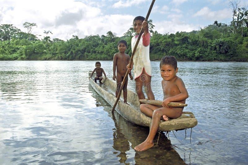 De Indische kinderen varen in dugout kano op Coco-Rivier stock afbeelding