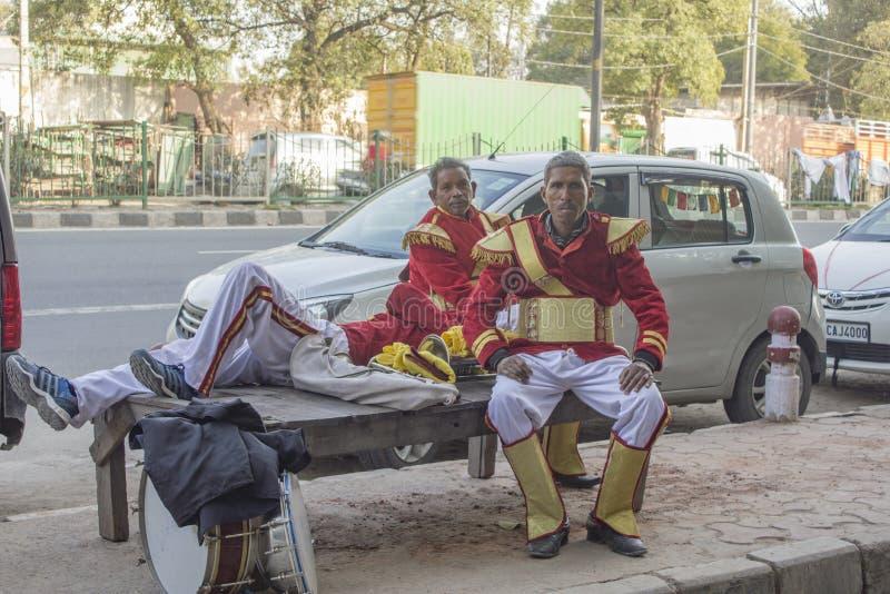 De Indische musici van straatuitvoerders met trommels in rode eenvormige kleding rusten op de bank royalty-vrije stock foto