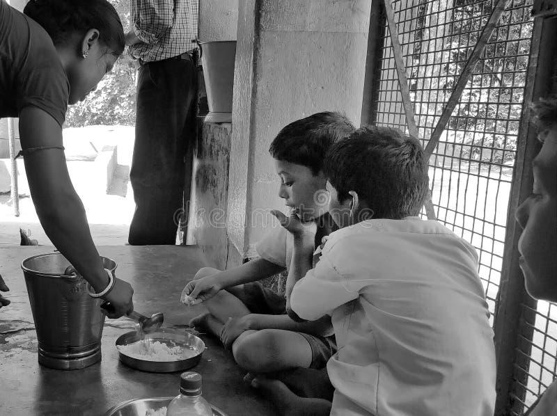 De Indische schoolkinderen eten hun vrije middagmaaltijd op een overheidsschool in Haryana stock fotografie