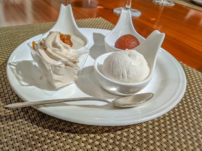 De Indische snoepjes gulab jamun, rasgulla, payesh en de room servered in stijl stock fotografie