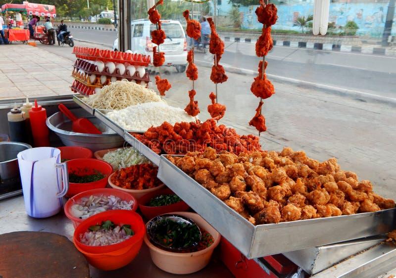 De Indische verkoper van het straatvoedsel klaar met ingrediënten om snel voedsel op kar te koken stock foto