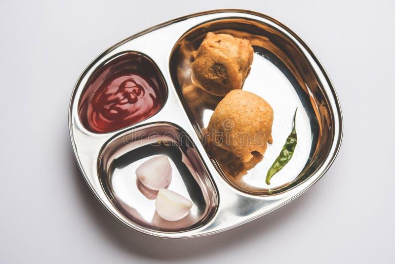 De Indische voedselsnack Aloo Bonda of aardappelpakoda of pakora dienden in een roestvrij staalplaat met tomatenketchup stock afbeeldingen
